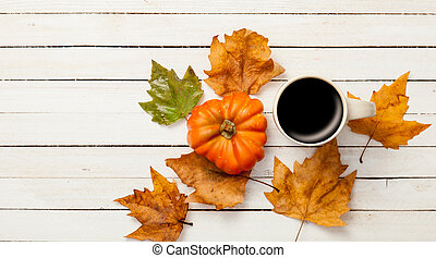 Cup and pumpkin with leafs