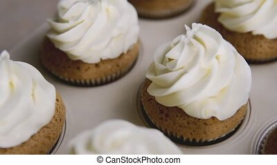 Cup-cakes with cream. Butter cream on tasty muffins, home...