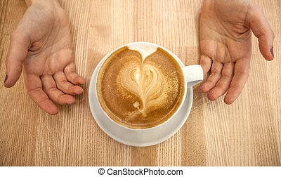 cup cappuccino with foam in the form of a heart and hands