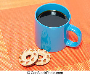 Cup coffee and two cookies on orange napkin