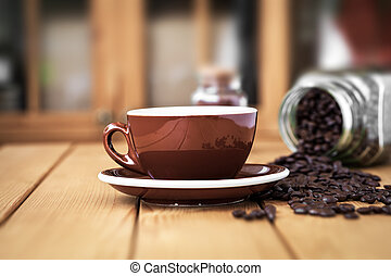 Cup coffee on a wooden table with scattered coffee beans
