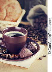 Cup coffee with beans and chocolate candies