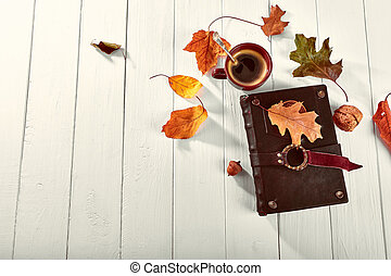 Cup coffee with book dry oaken leaf