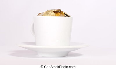 Cup filled with coins - White cup on saucer filled with...