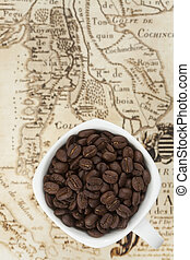 Cup full of coffee beans on the old map