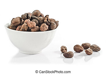 Cup full of shea nuts on white background