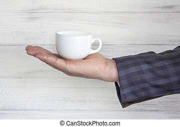 cup in the businessman's hand. Coffee and tea