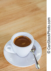 Cup of an espresso coffee on a wooden table