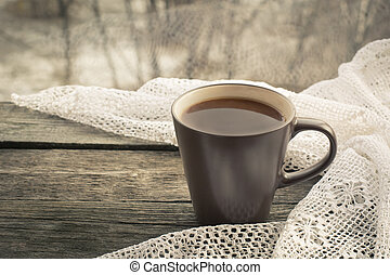 Cup of black coffee and a lace in front of the window on the wooden background.