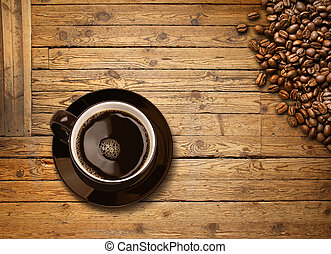 Cup of black coffee and beans on old wooden table
