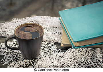 Cup of black coffee and book in front of the window.