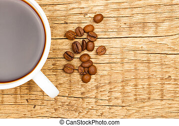 Cup of black coffee and coffee beans on old wooden table