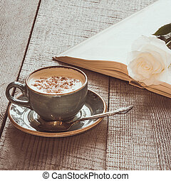 Cup of black coffee and open book with white rose on wooden board. Vintage toned. Close up.