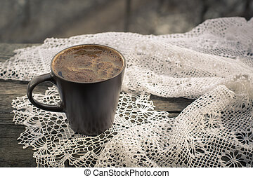 Cup of black coffee in front of the window and lace on wooden background.