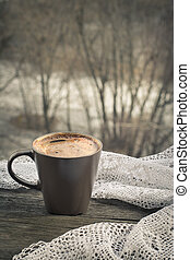 Cup of black coffee in front of the window and lace on wooden board.