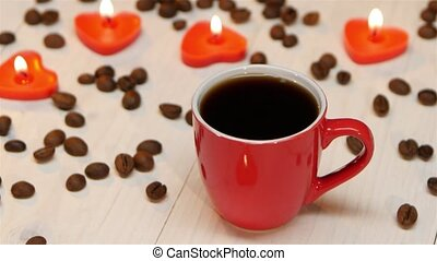 Cup of black coffee on a background of candles