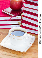 cup of black coffee on table with books