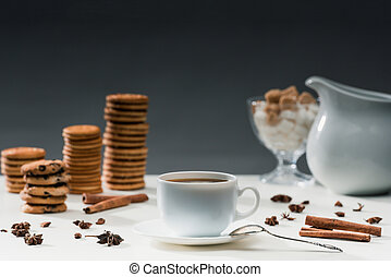 Cup of black coffee on table with cookies and spices