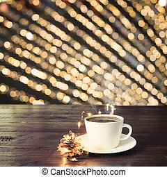 Cup of black coffee on wooden board in cafe. Blurred gold garland as background. Christmas Time.
