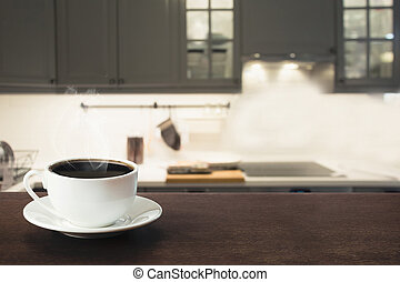 Cup of black coffee on wooden tabletop in blurred modern kitchen. Close up. Indoor.