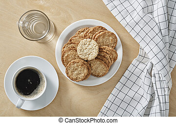 Cup of black coffee whit cookies, glass of water on white plate and wooden background. Top view.