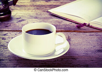 Cup of black coffee with a book