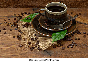 Cup of black coffee with beans and green leaves