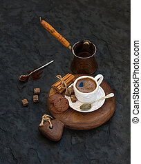 Cup of black coffee with chocolate biscuits, cinnamon sticks and cane sugar cubes on rustic wooden board over dark stone backdrop.