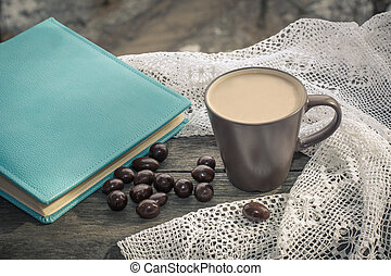 Cup of black coffee with milk and chocolate candy in front of the window in the morning.