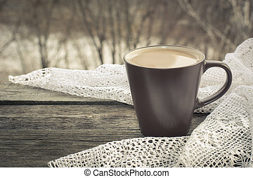 Cup of black coffee with milk in front of the window and a lace on the wooden background.