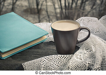 Cup of black coffee with milk in front of the window in the morning