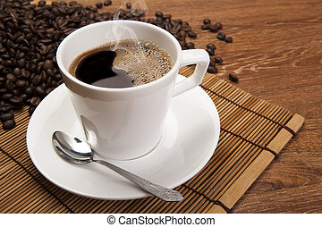 cup of black coffee and roasted coffe beans close up