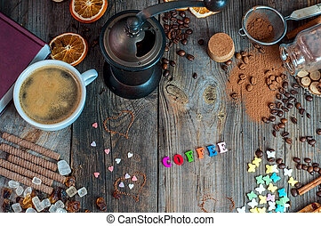 cup of black coffee with sweets and spices on a gray wooden surface