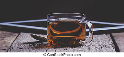 Cup of black hot tea with spoon and digital tablet on the old wooden table, breakfast, selective focus and toned image