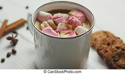 White mug filled with sweet cacao and marshmallows served on table with cookies and spices