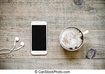 Cup of cafe latte with smartphone and earphones on wooden table