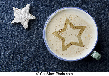 Cup of cappuccino coffee with foam in the form of star on blue jeans, denim background. White wooden star.