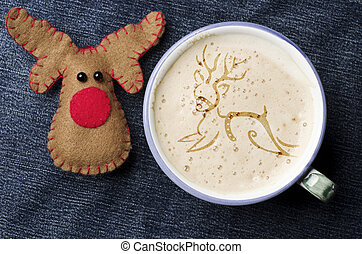 Cup of cappuccino coffee with foam in the form of reindeer on blue jeans, denim background. Rudolph reindeer craft handmade from felt.