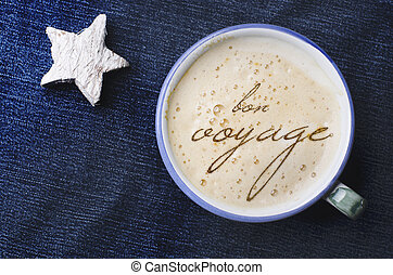 Cup of cappuccino coffee with foam in the form of words in French bon voyage on blue jeans, denim background. White wooden star. Have a good trip.