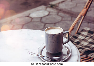 Cup of cappuccino on an iron tray on a table in a street cafe
