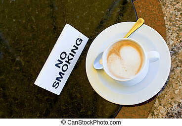 cup of cappuccino  on no-smoking table