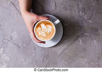 Cup of cappuccino with figure cream