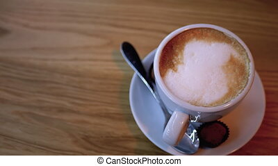 Cup of Cappuccino with White Foam on the Wooden Table in the Restaurant. Close-up