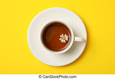 Cup of chamomile tea on yellow background