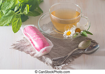 cup of chamomile tea with pink eclair