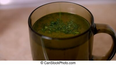 Cup of chicken broth with herbs