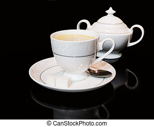 Cup of coffe and sugar bowl on black background