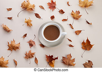 Cup of coffe with dry autumn leaves on biege background. Top view flat lay.