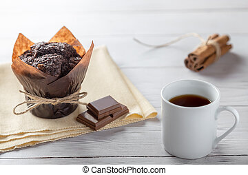 Cup of coffe with homemade muffin, chocolate and cinnamon on wooden table