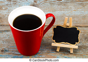 Cup of coffee and a blackboard with empty space for a text on wooden background